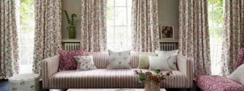 Country cottage style living room with stripey couch and floral curtains