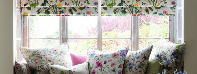 window seat with cushions and colourful blinds