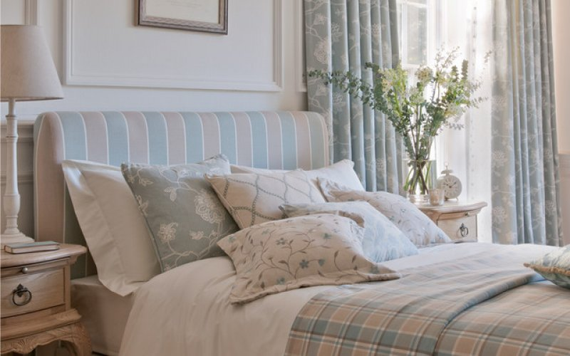 country cottage style bedroom with a thick quilt and curtains